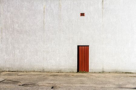 Red door in the middle of a gray concrete wall. Architecture background.