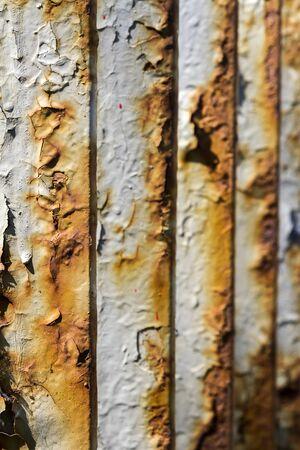 Close up of old rusty iron bridge railing. Peeling paint on metal.