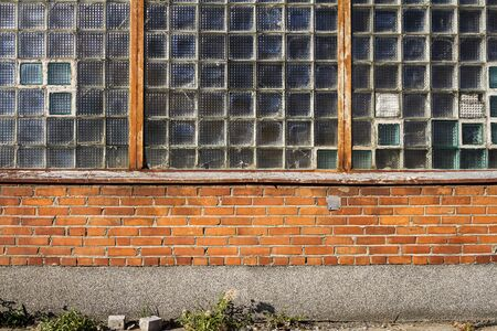 Red brick wall with glass block window. Architecture detail.
