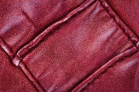 Crumpled red leather texture background. Abstract texture of leather with a seam. 版權商用圖片