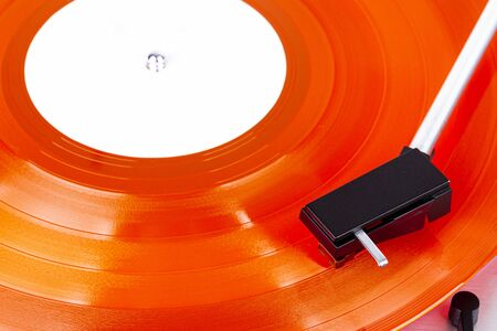Close up of turntable needle on a vinyl record. Turntable playing vinyl. Needle on rotating red vinyl. Stockfoto