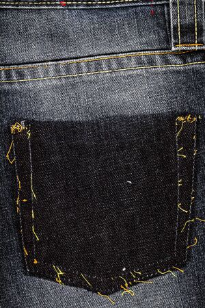 Black jeans fabric with ripped of pocket background. Jeans detail. Black jeans texture background.