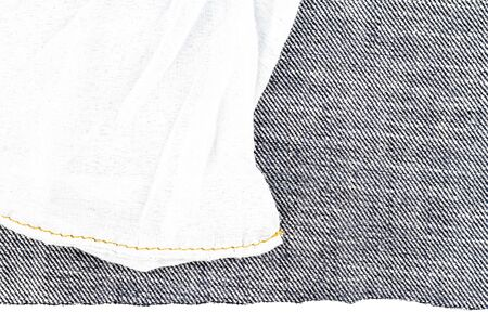 Piece of black jeans fabric isolated on white background. Rough uneven edges. Denim jeans torn. Back side of jeans fabric 免版税图像