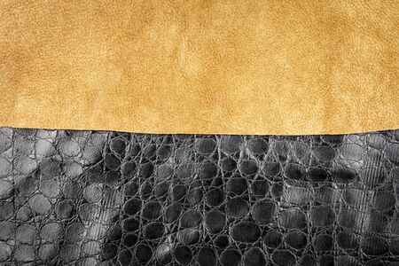 Brown leather and black artificial alligator skin textures background.