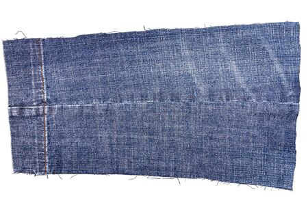 Piece of blue jeans fabric isolated on white background. Rough uneven edges. Denim pants torn.