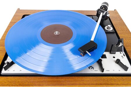 Vintage turntable with a blue vinyl isolated on white. Wooden plinth. Retro audio equipment. Фото со стока