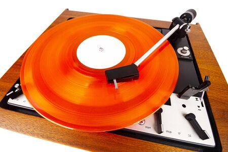 Vintage turntable with a red vinyl isolated on white. Wooden plinth. Retro audio equipment. Archivio Fotografico