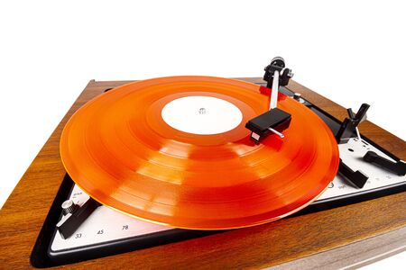 Vintage turntable with a red vinyl isolated on white. Wooden plinth. Retro audio equipment. Фото со стока
