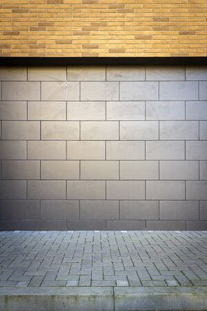 Modern tile and yellow brick wall with a sidewalk