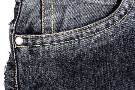 Piece of black jeans fabric with a side pocket isolated on white background. Rough uneven edges. Denim jeans torn