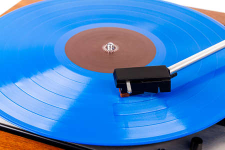 Close up of turntable cartridge on a vinyl record. Turntable playing vinyl. Needle on rotating blue vinyl.