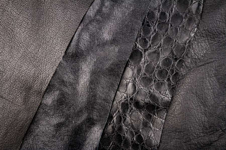 Black leather and fake artificial alligator skin textures background.