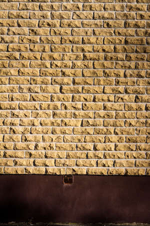 Yellow brick wall background with a ground