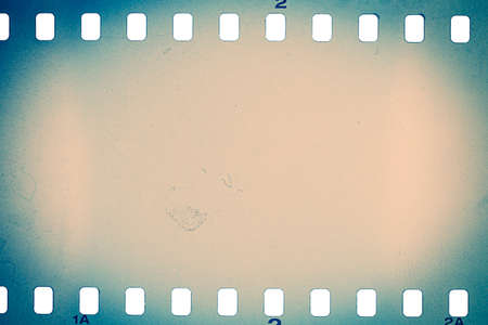 Dusty and grungy 35mm film texture or surface. Perforated camera film isolated on white background. Standard-Bild