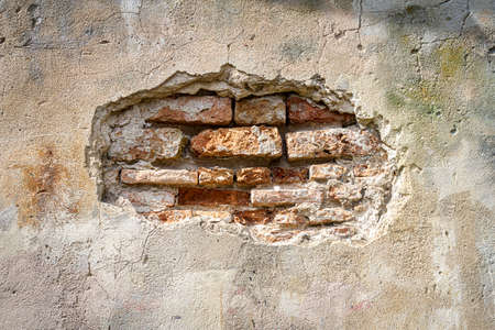 Old brick and plaster wall texture background. Painted distressed wall surface. Messy building facade with damaged plaster.