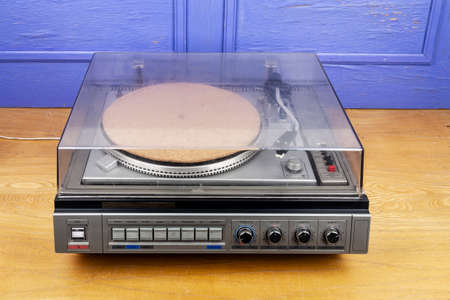 Vintage turntable vinyl record player with dust cover on table by blue wall. Foto de archivo