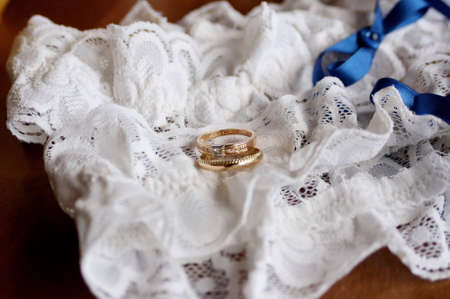 borrowed: a detail of a brides garter with wedding rings Stock Photo