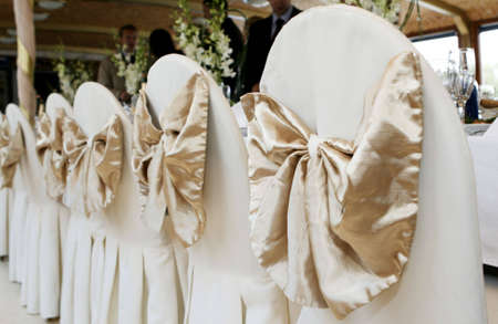 rentals: chairs set up for a wedding, wrapped in white satin with bow