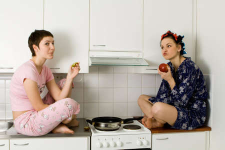 two young woman sitting in the kitchen and eating an apple Stock Photo - 4822744
