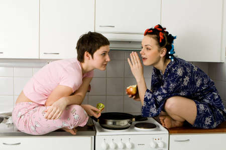 girl telling a secret to another - gossip sitting in the kitchen photo