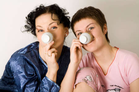 friends having tea series: two young woman sitting at a table and having fun