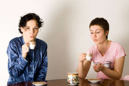 friends having tea series: two young woman sitting at a table and drinking tea Stock Photo