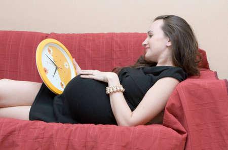 pelirrojas: Mujer embarazada con un reloj Foto de archivo