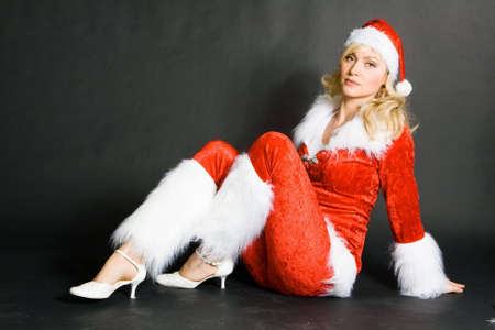 sexy beautiful blond girl dressed as Santa against black background photo