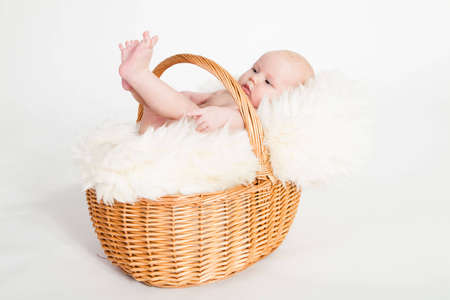 A beautiful baby girl with cute facial expression lying in a basket - two months old Stock Photo - 6628329
