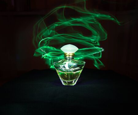 perfume spray: Perfume bottle and green light painting on the black background Stock Photo