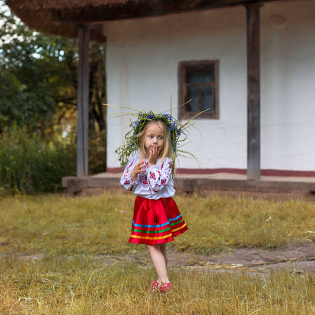 national costume: little girl in couronne from flowers in national costume