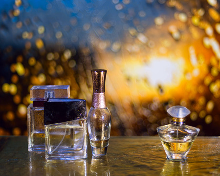 Perfume bottles under the rain with water drops on the golden table Фото со стока - 38319473