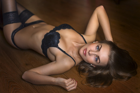 sex pose: Seductive brunette model on the floor laying in underwear