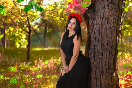 chaplet: Black haired gothic woman in the chaplet of red flowers at the colorfull nature background Stock Photo