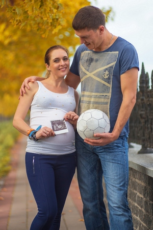 sonograma: Pregnant couple at the autumn park hugs with sonogram picture of baby