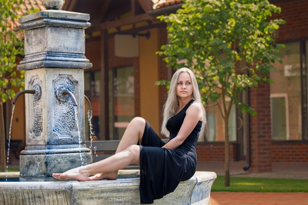 Beautiful blonde woman sitting on the old drinking fountain barefoot at the european street in the long black dress.