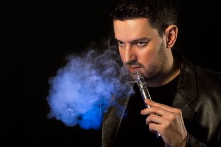 background e cigarette: Black haired handsome man vaping e-cirarette custom mod - isolated on black background