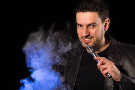 mod: Handsome man smiling with e-cigarette custom mod and vapor - on the black background Stock Photo