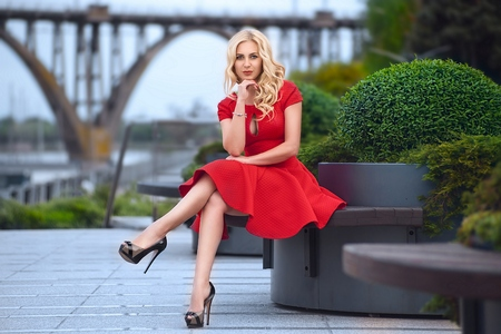 Beautiful blonde woman in red dress and high heels is sitting outdoor on the bench at the evening. Stock Photo