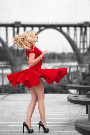 Beautiful blonde woman in the red dress and high heels dancing on the wind at black and white outdoor