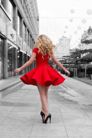 Beautiful blonde woman in the red dress and high heels walking down at black and white outdoor