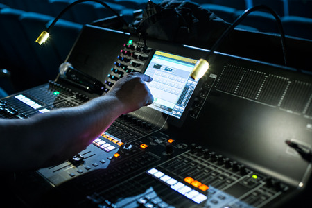 Large modern show sound controller with lighted screen, operators hand and ajusted presets - close up photo