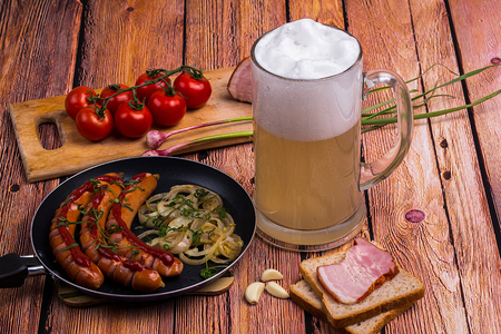 unfiltered: Glass mug with unfiltered white beer with fried sausages, tomatoes chery, bread, garlic and pork meat on the old wooden table