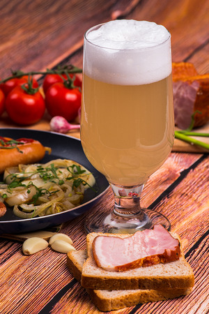 unfiltered: Tall elegant glass with unfiltered white beer with fried sausages, tomatoes chery, bread, garlic and pork meat on the old wooden table - close up portrait photo