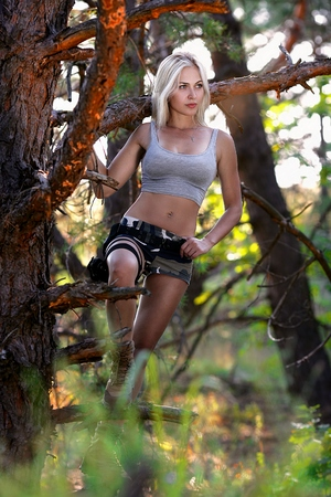 camouflage woman: Portrait of beautiful blonde woman in camouflage on the forest background