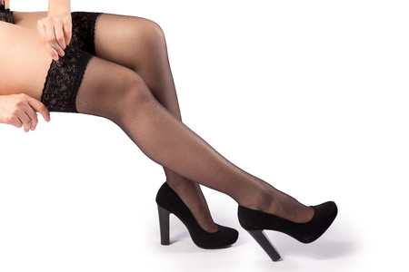 black stockings: Woman putting on black stockings and high heels isolated on the white background