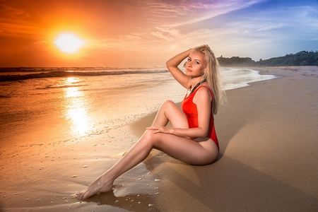 Pretty woman in the red swimsuit with long legs sitting on the lonely evening beach in the rays of setting sun. Wide angle shot photo with double light exposition. Stock Photo