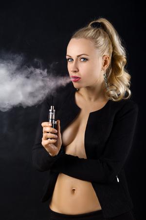 Beautiful woman vaping e-cirarette mod - blowing cloud of vapor Фото со стока