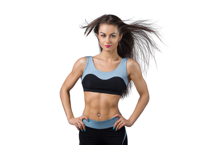 Portrait of the fitness girl in the sports costume on the white background with winded hair. Beauty fitness portrait. Stock Photo