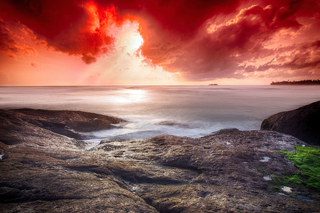 infernal: Infernal sunset in the ocean - wide angle landscape photo of ocean waves with long exposure. Stock Photo